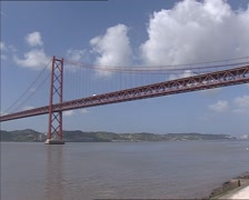Pan + hold suspension bridge 25 de Abril Bridge crossing the Tagus river Stock Footage