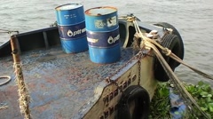 Two oil barrels on the bow of a small cargo boat in Asia Stock Footage