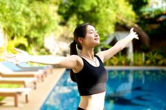 asian girl open arms relaxing at pool - stock photo