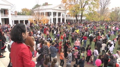 Halloween festivities wide shot of crowd and buildings exterior afternoon Stock Footage