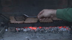 Lunch cooking, closeup hand turning meat on grill outdoor, barbecue in family Stock Footage