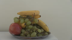 White wall background, basket fruits, grapes apples, closeup hand peeling banana Stock Footage
