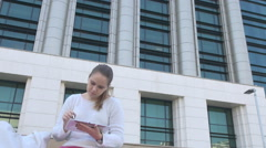 Young girl outside with tablet, online generation people, business building view Stock Footage