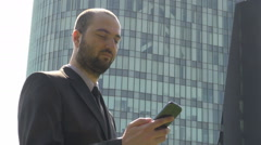 Businessman talking on smartphone, career young boy with mobile phone outdoors Stock Footage