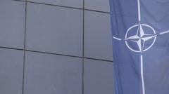 Big NATO flag looping waving in wind blow outside landmark building, HD shot Stock Footage