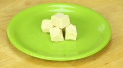 Slices of tofu rotate on a green plate Stock Footage