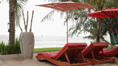 Red Loungers Under Parasol 2 Stock Footage