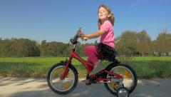 HD Slow-Mo: Cheerful Little Girl on Red Bike Stock Footage