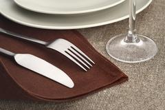 Table setting. Cutlery set with fork, knife, plate and glass on brown linen napk - stock photo