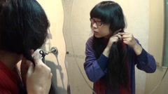 Asian woman plaiting her hair near the mirror - stock footage