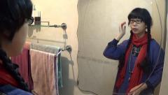 Asian woman fixing her hair near the mirror Stock Footage