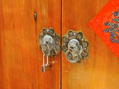 Ancient knockers and modern lock closeup in Taiwan - stock photo