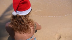 Beautiful Woman in Santa Hat Writing 2015 New Year on Sand at Beach. Stock Footage