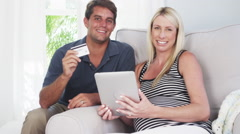 Excited parents smiling at camera with credit card Stock Footage