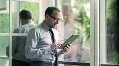 Businessman standing next to the window and using tablet Stock Footage