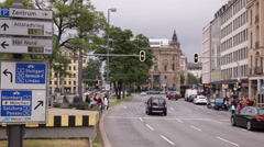 Munich City Center Cars Passing Traffic People Crossing Busy Road Direction Sign Stock Footage
