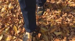 Woman foot walking yellow leaves urban sidewalk autumn season forest road leaf Stock Footage