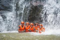 happy tourists abseil in datanla waterfall, vietnam - stock photo
