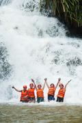 Happy tourists abseiling in datanla waterfall in vietnam Stock Photos