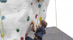 Courageous Young Boy Climb Up Artificial Rock Wall Kids Playground Outdoor Park - stock footage