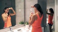 Woman, combing hait in the bathroom and looking at oneself in the mirror Stock Footage