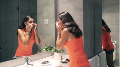 Woman checking and examinating her skin in the mirror - stock footage