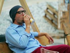 Stylish man drinking beer on bench, steadycam shot Stock Footage