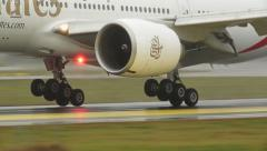 Emirates Boeing 777 landing detail view of landing gear touchdown Stock Footage