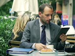 Businessman drinking coffee and reading news on tablet Stock Footage