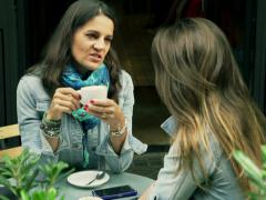 Women talking in the street cafe and drinking coffee, steadycam shot - stock footage