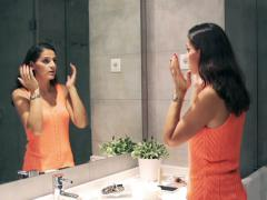 Woman checking and examinating her skin in the mirror Stock Footage