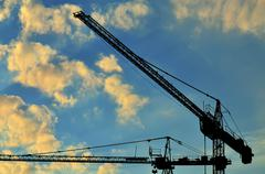 Construction cranes against of the sun Stock Photos