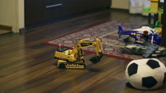 Digger toy moving on the floor, steadycam shot, slow motion Stock Footage