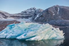 Blue glacier ice in the Arctic fjord - stock photo