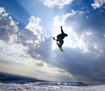 silhouette the snowboarder jumping high in the blue sky and clouds - stock photo