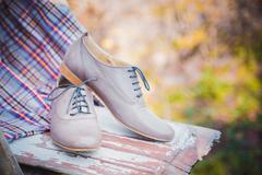 women's leather shoes with laces are on a checkered tablecloth - stock photo