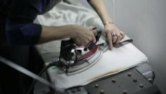 Woman at clothing factory ironed. Close up Stock Footage