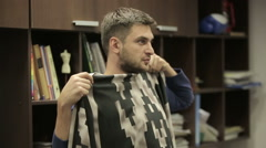 Man tries fabric for clothing. Office of the designer. Stock Footage
