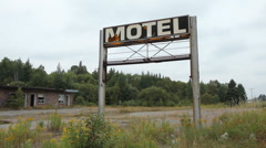 Broken Motel sign and wrecked motel in background. Stock Footage