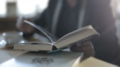 A man in a cafe drinking coffee and reading a book. Slow motion Stock Footage