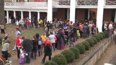 Halloween families and kids line up for trick or treating exterior afternoon. Stock Footage