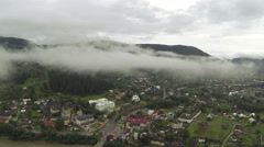 Flight among clouds over mountain village. Aerial   - stock footage
