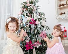 two girls decorate a  christmas tree - stock photo