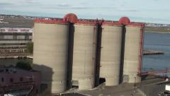 Four silos on the coast shot from a passing ship - stock footage