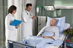 Two doctors with a male patient in a hospital ward - stock photo