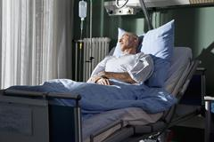 A man sleeping in a hospital bed Stock Photos