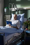 A man reading a book in a hospital bed Stock Photos