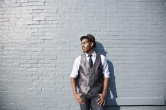 A young black man leaning against a brick wall - stock photo