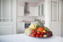 Fruits and vegetables in plate on table at home Stock Photos