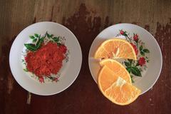 Directly above shot of chili powder and orange slice served in plates on table Stock Photos